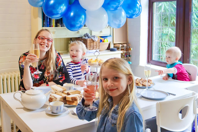 A birthday tea party with cake stand and champagne, children holding drinks up to the camera and blue balloons