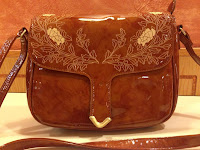 Brown shoulder bag with floral detailing on the top flap