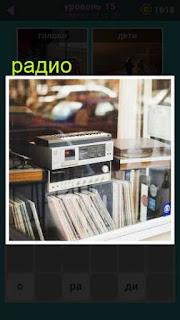 в комнате на полке стоит обычное радио и книги под стеклом