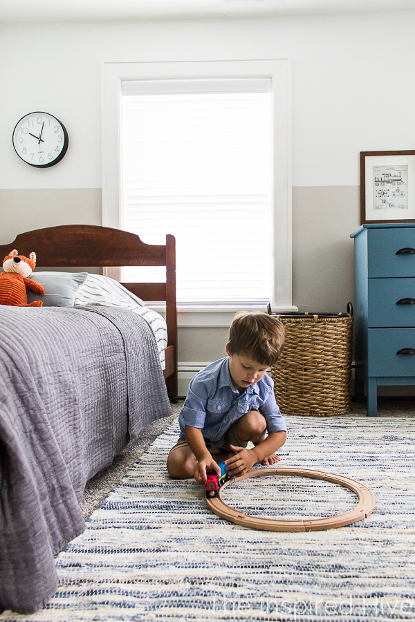 Playing with toy trains in boy's bedroom. Denim rug and antique bed.