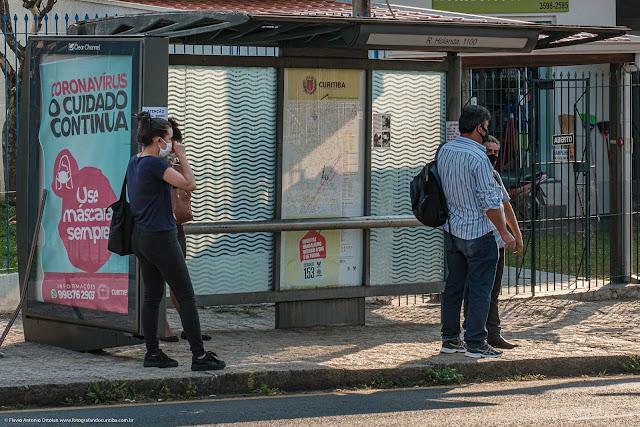 Pessoas em um ponto de ônibus. Todas com máscara