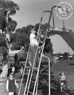 白黒の写真。子供たちが遊んでいる。その奥にスレンダーマンがいる。