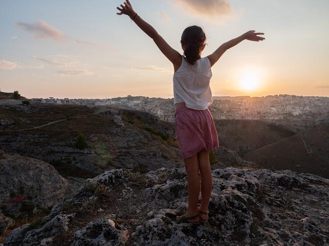 Niña de espaldas al atardecer con vistas a la ciudad de Matera