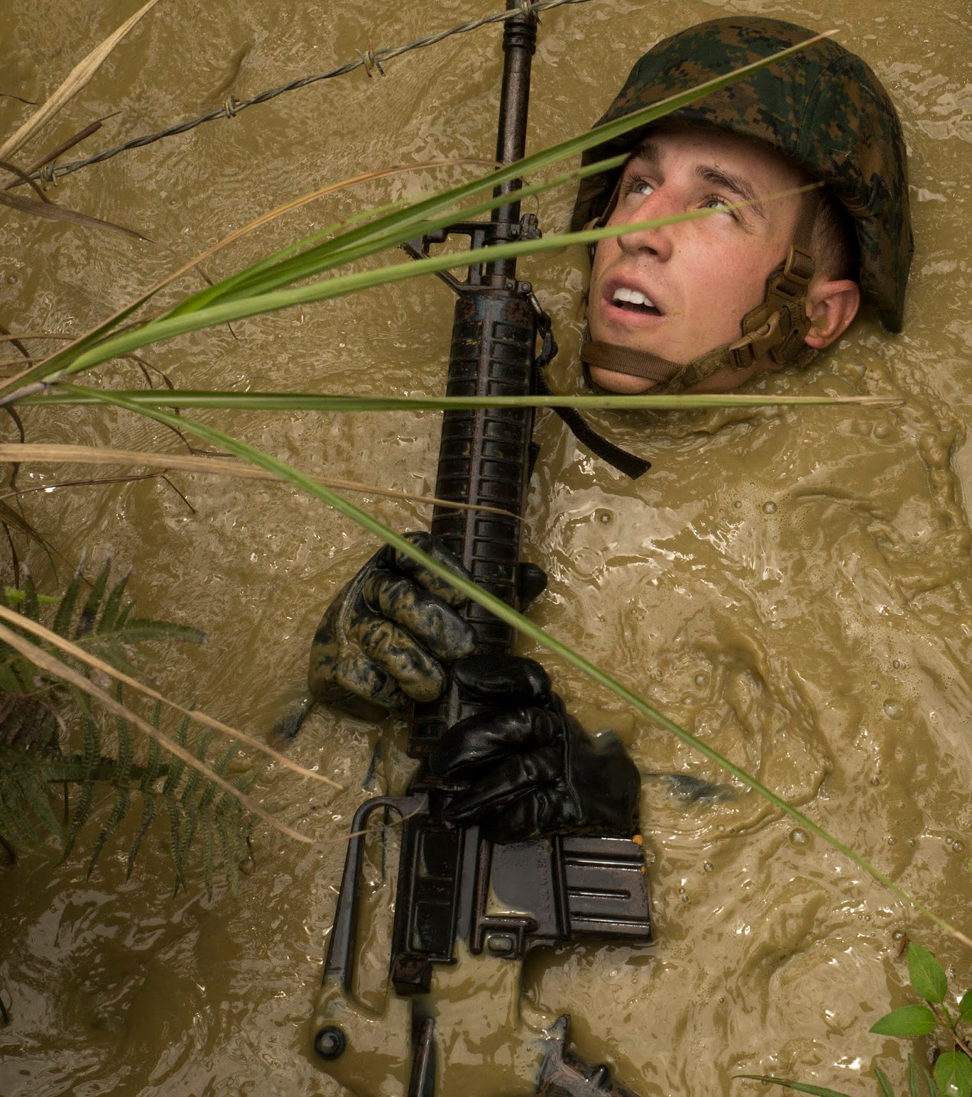 A man in military gear is nearly submersed in dirty water with only his face, hands, and gun, above the water