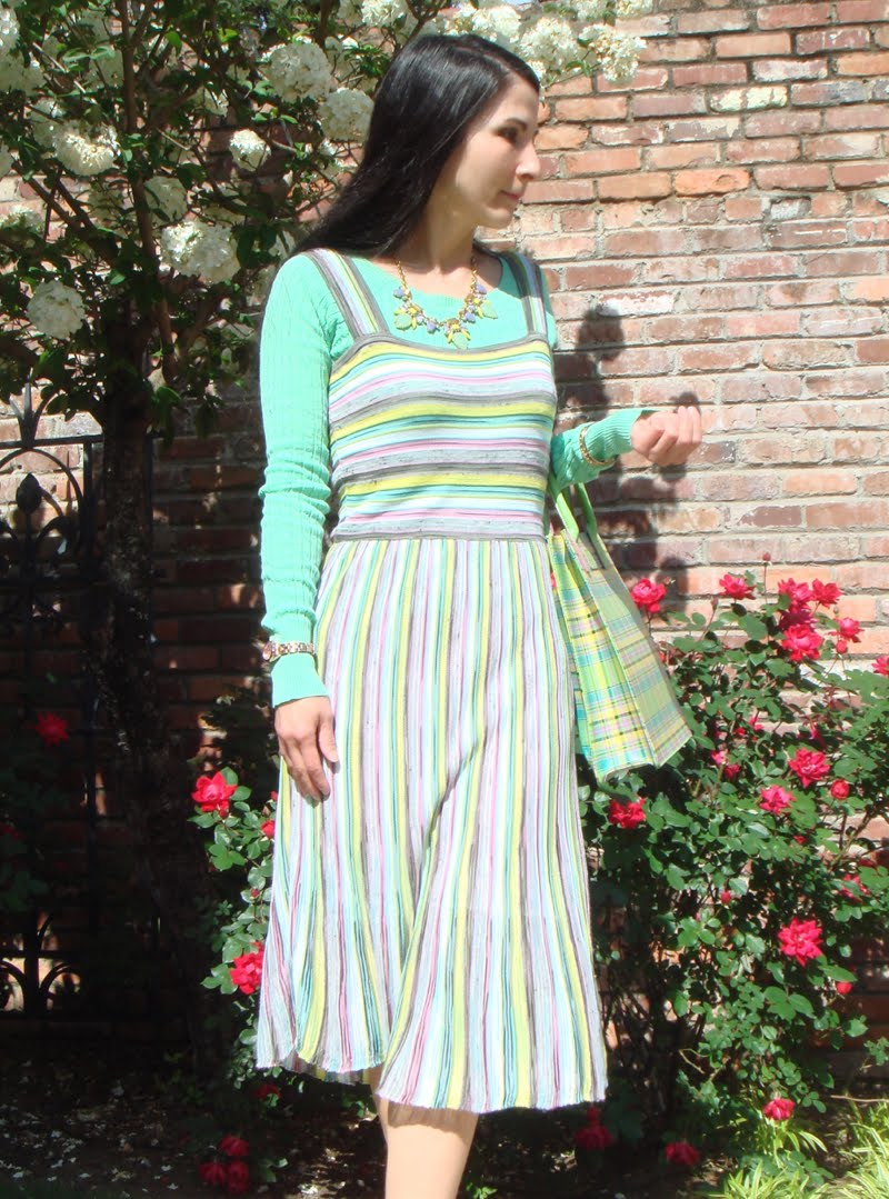 Wearing pastel striped dress, green sweater, statement necklace and holding pastel plaid bag.