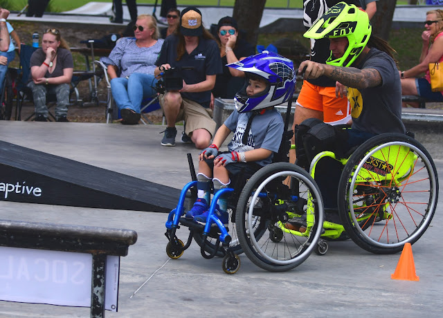 A man in a bright green wheelchair with a matching motorcycle helmet, is shown pushing a boy in a small, blue, manual wheelchair. The boy is wearing a blue, motorcycle helmet.