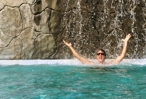 Greg White under a pool's watefall