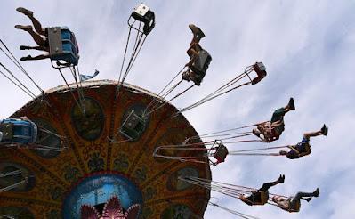 Orang-orang menikmati perjalanan di kursi roda di sebuah pekan raya kecil di Munich, Jerman selatan, pada 3 Juli 2021, di tengah pandemi virus corona (Covid-19) yang sedang berlangsung. - Pengunjung pameran wajib memakai masker selama kunjungan mereka dan di perjalanan. AFP