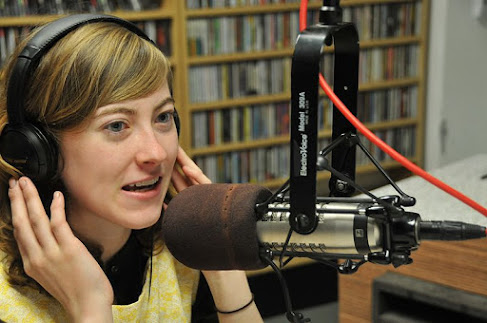 Woman wearing headphones and speaking into a large microphone