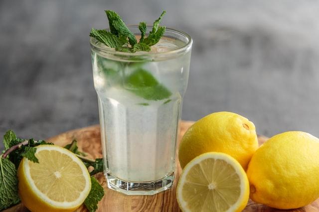 Varios limones amarillos enteros y partidos alrededor de un vaso de vidrio con agua de limón sobre una tabla de madera