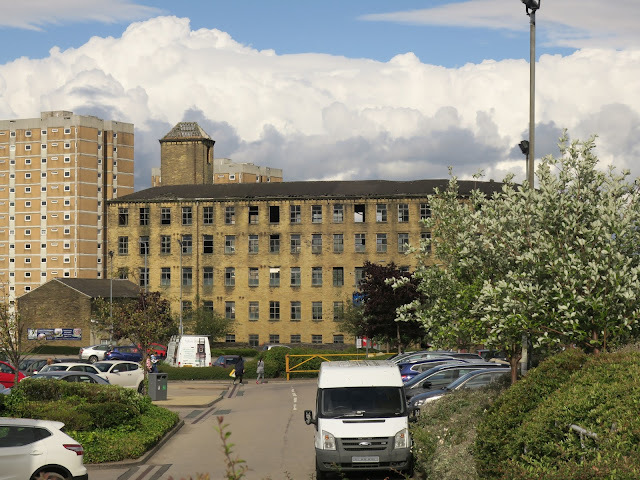 Pellon Lane Mill with blocks of flats behind and car-park in front.