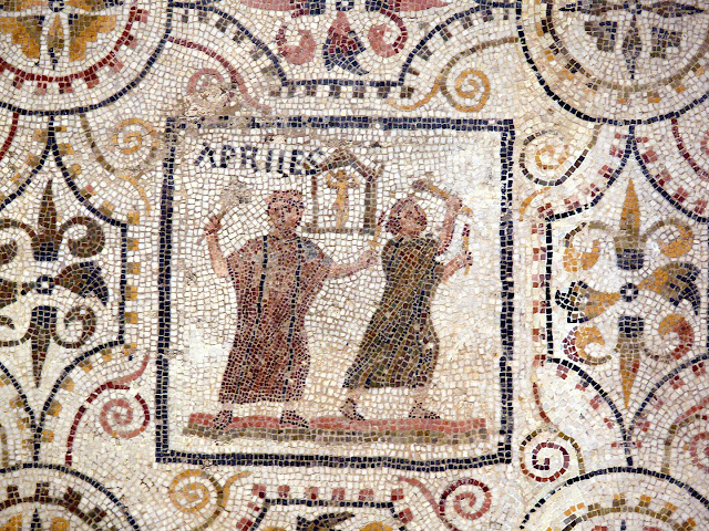 "Roman mosaic image depicting to figures surrounded by geometric/floral motifs and the wordand the word ""Apries""."