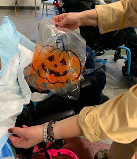 Teacher's hands holding large ziploc bag with jack-o-lantern outline and orange paint inside next to student