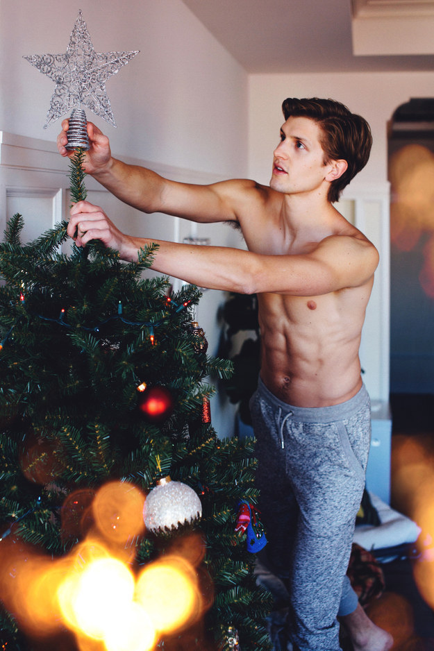 shirtless-boy-putting-christmas-star-ornament-tree