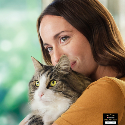 Brunette woman holding long-haired grey-and-white cat
