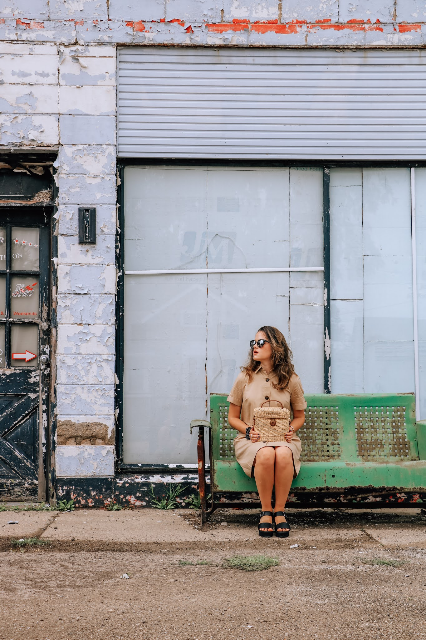 Fashion blogger Kathleen Harper posing as a young stylish woman waiting for the bus in a photo shoot.