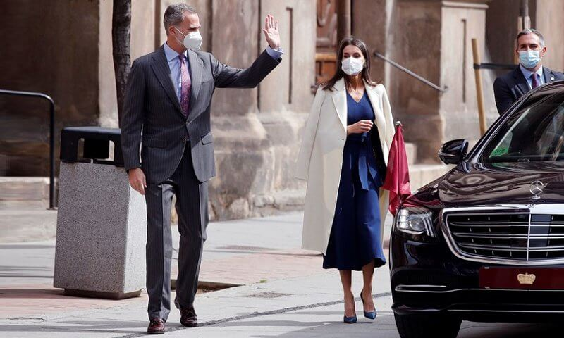 Queen Letizia wore a navy belted wool v-neck midi dress from Massimo Dutti, and white cashmere coat from Carolina Herrera