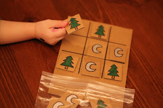 Child toddler playing DIY tick-tac-toe game reduce reuse recycle