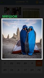 двое людей стоя одели спальный мешок на себя около палатки