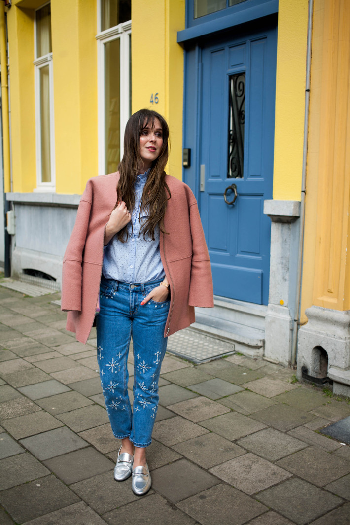 Outfit: embroidered jeans, pink coat, yellow wall