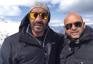 Ajay Devgn with a crew Member