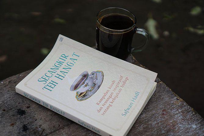 Membaca buku dengan menyesap kopi