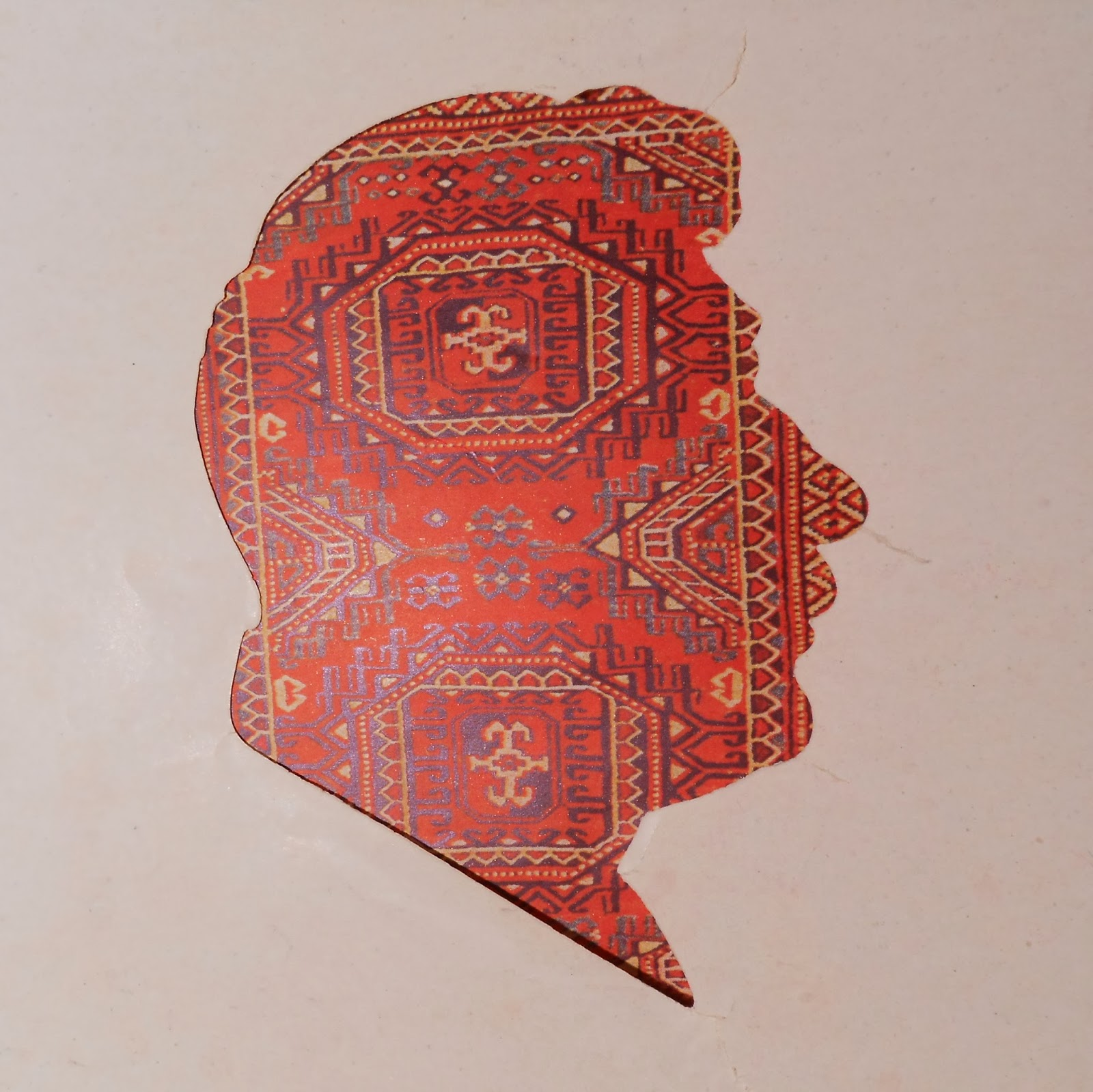 The silhouette of a man's profile, filled in with a red textile pattern.