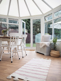 Turn an old unused conservatory into a stylish sunroom with dining table and chairs and blanket box seating area from The Cotswold Company