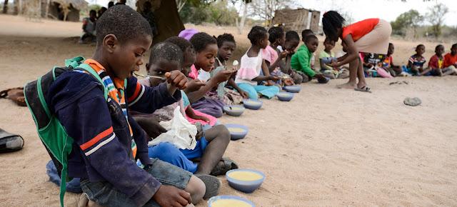 Niños comiedo en una escuela de la provincia de Maputo en Mozambique.UNICEF/UN051605/Rich