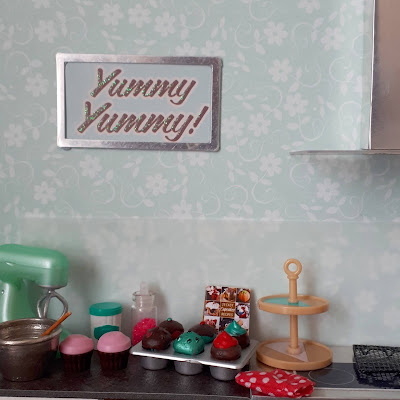 One twelfth scale modern miniature kitchen bench containing an electric mixer, a bowl with wooden spoon, several iced and decorated cupcakes, a cupcake recipe book, a cake stand and a cooling rack. On the wall above the bench is a framed poster of the words 'Yummy yummy!'
