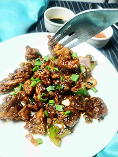 Serving chicken manchurian with a fork, chilly and soya sauce in background