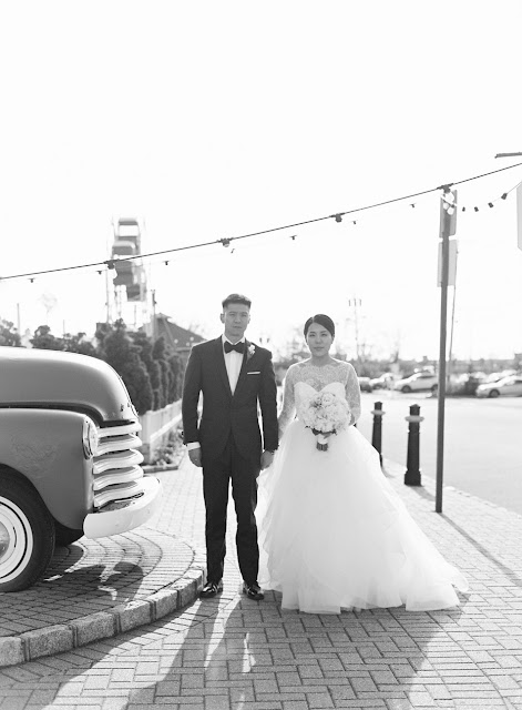 Jin and Christopher pose in their tuxedo and wedding gown next to a classic car on a cobblestone street before heading to Bridgeview Yacht Club