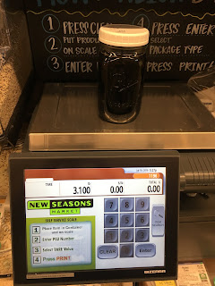 Photo of weigh station at bulk shopping area of New Seasons Market with a quart mason jar of Bragg's Aminos on the scale. https://trimazing.com/