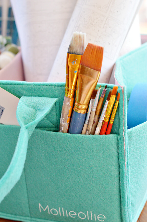 Paint brushes in teal storage caddy