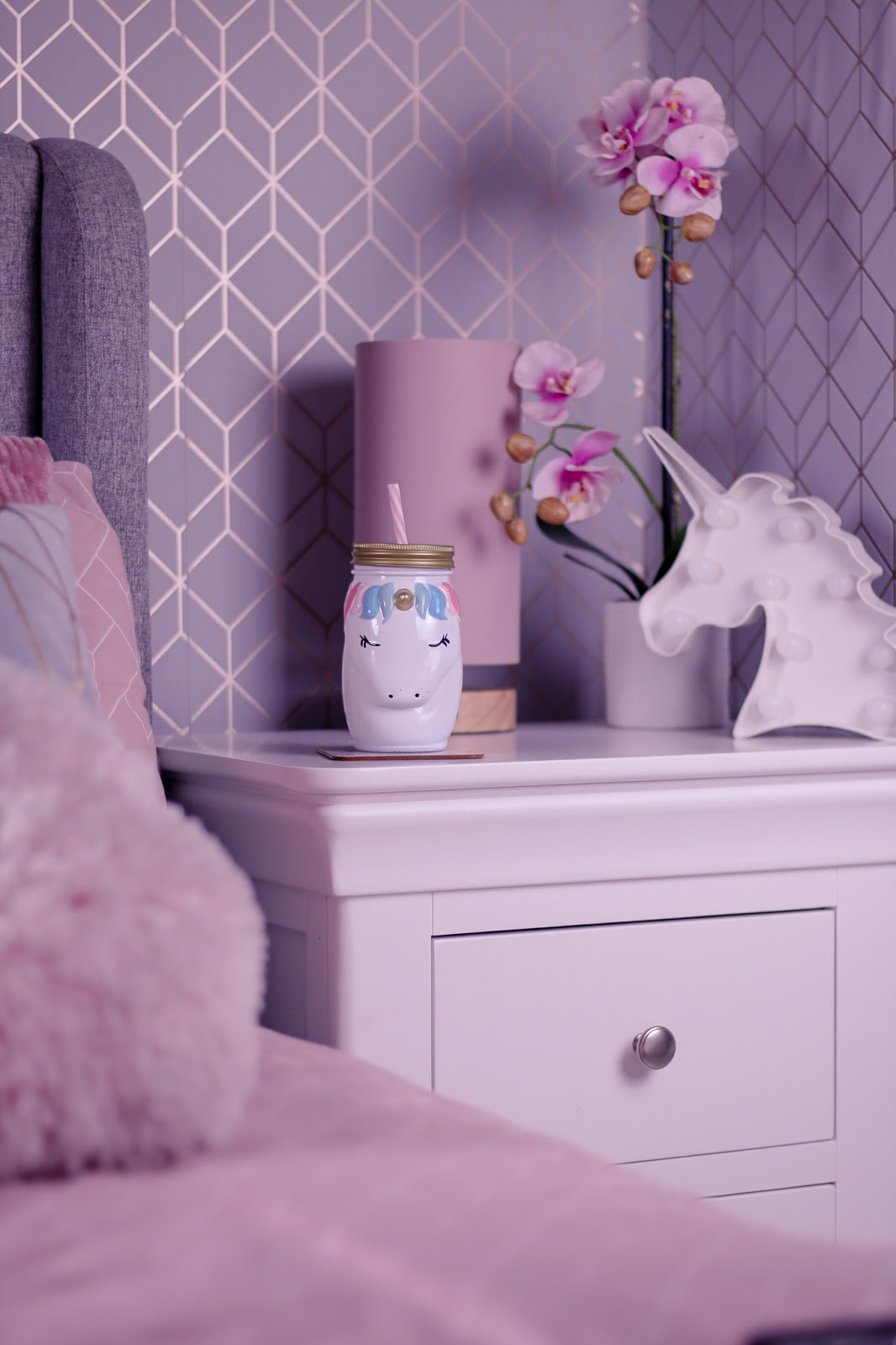 Photo of a unicorn cup on a white bed side table with a pink lamp, white unicorn LED light and pink faux orchid behind the cup.