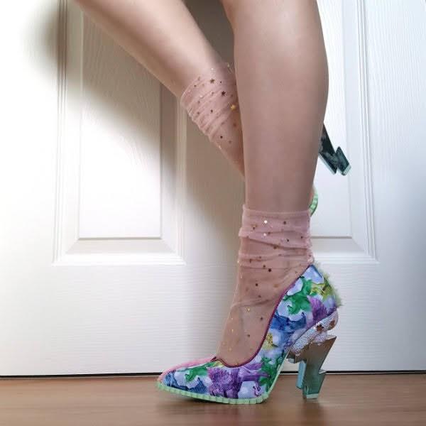 behind leg raised showing lightning bolt shaped heel of shoe with unicorn print shoe on foot on floor