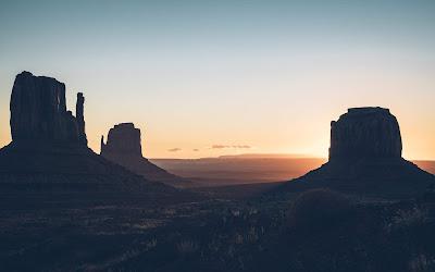 Desierto con montañas negras y sol de fondo