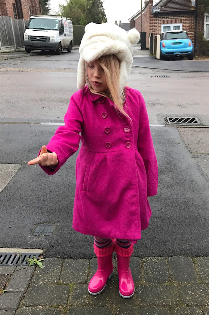 A 5 year old girl standing on a residential street with her hand out trying to catch a snowflake on her finger