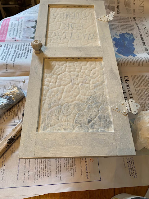 Photo of a small door being painted off white