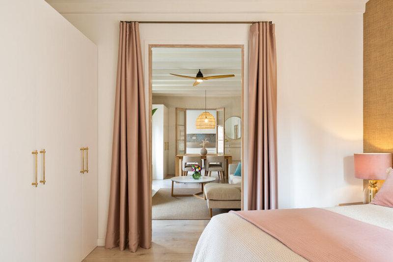Dormitorio abierto al salón con cortinas