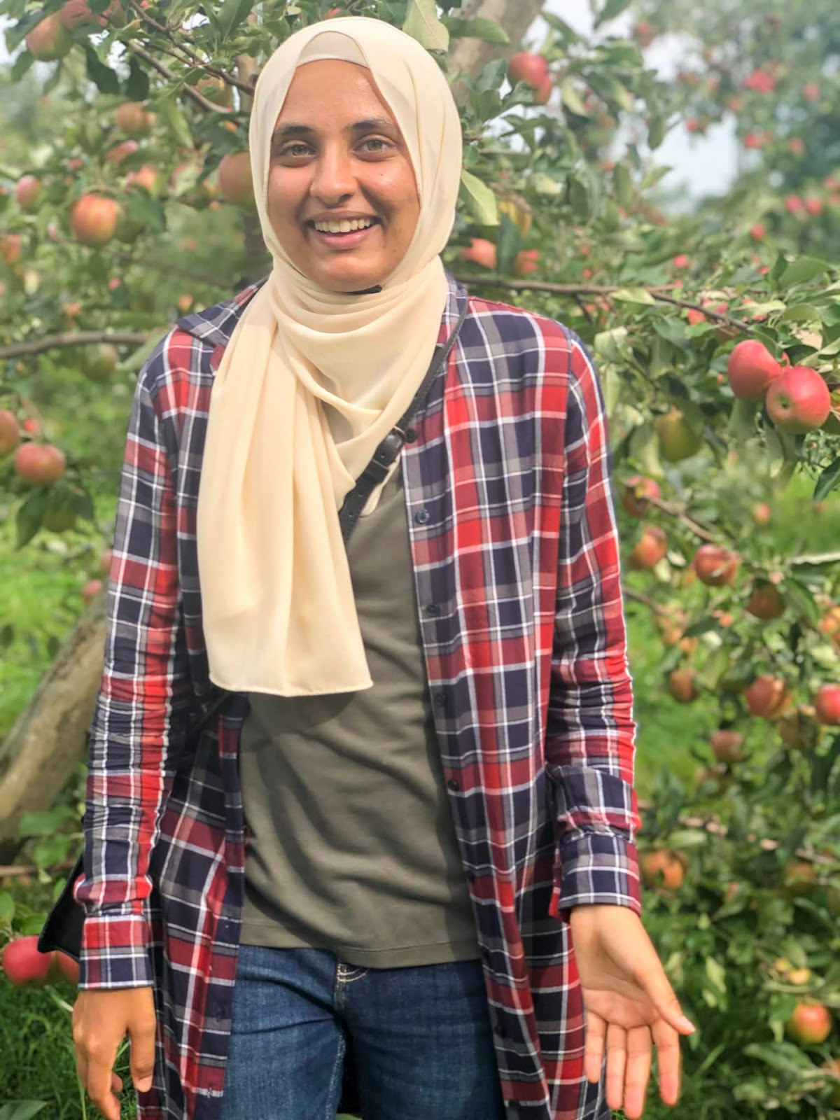 Sahara smiling in front of an Apple Tree