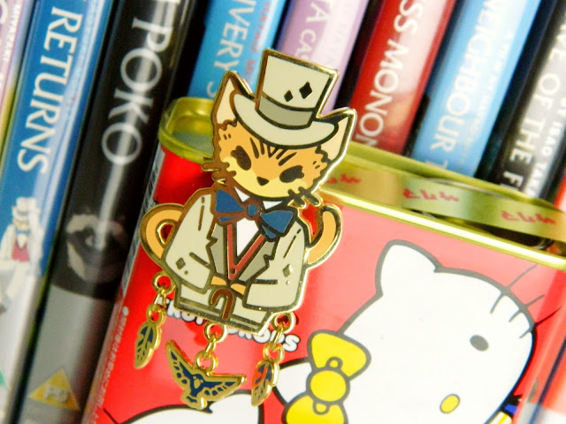 An enamel pin of a cat in a suit from the movie The Cat Returns