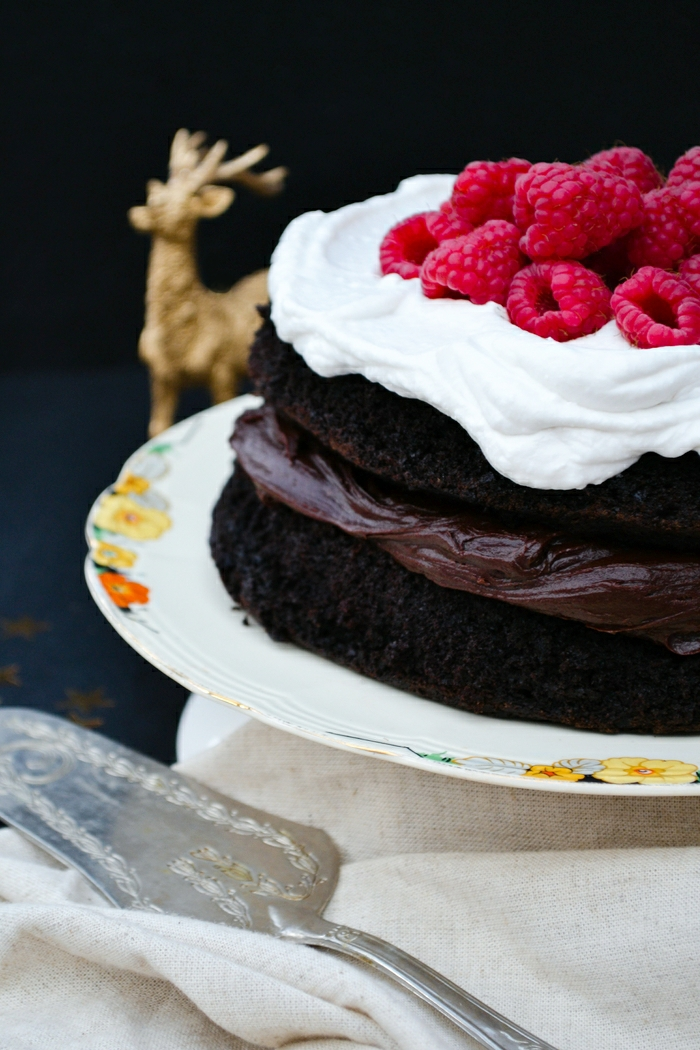 An indulgent chocolate cake filled with chocolate buttercream and topped with whipped coconut cream and raspberries. Suitable for vegetarians and vegans.