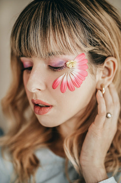 Blonde girl wearing make up and pink flower petals on her face.