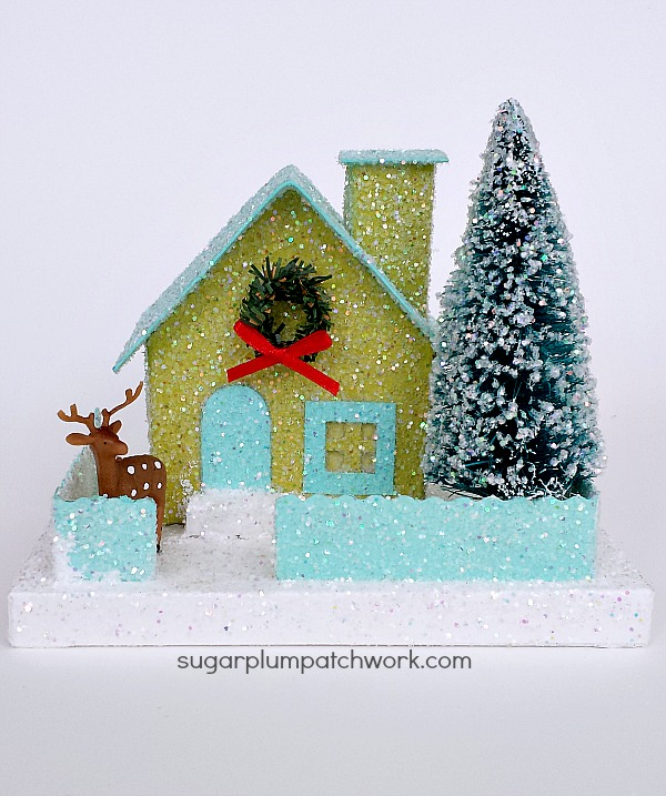 green glitter house with tree and deer