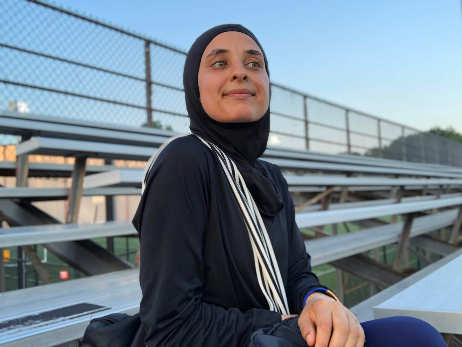 Sahara sitting on a bench at the track with track bag, smiling at camera in black nike hijab