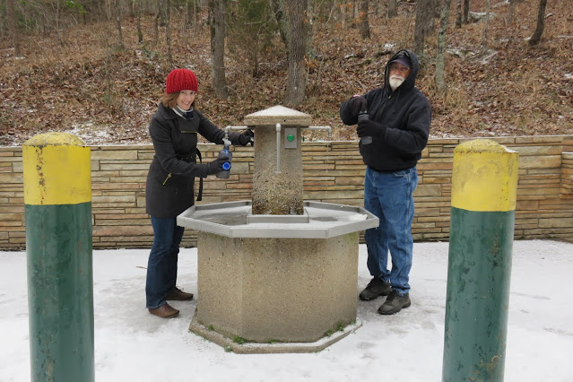 woman and old man at water fountain