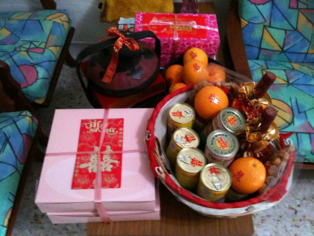 consists of gifts wrapped in red paper, cans of pork, orange