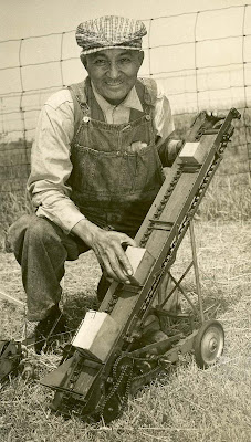 An older African American man in cap, collared shirt,  and overalls outdoors holding a small piece of farm machinery with wheels and a chain on an incline