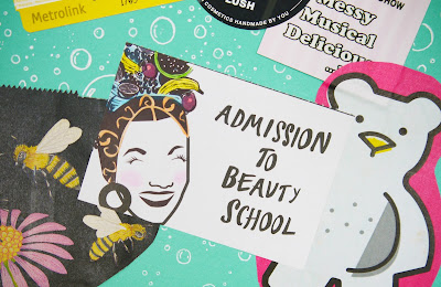 teal scrapbook page with a LUSH beauty school ticket in it, and a picture of LUSH butter bear